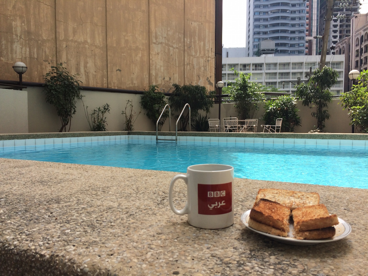 photograph of cup of coffee and plate of toast by a swimming pool