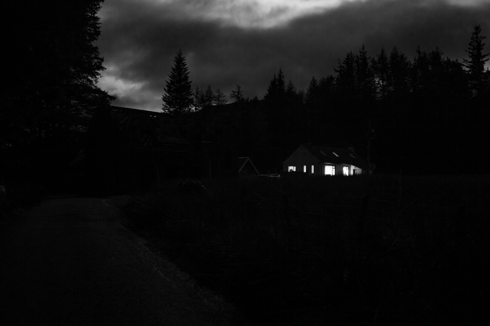 Dark, moonlit image of a small house surrounded by trees