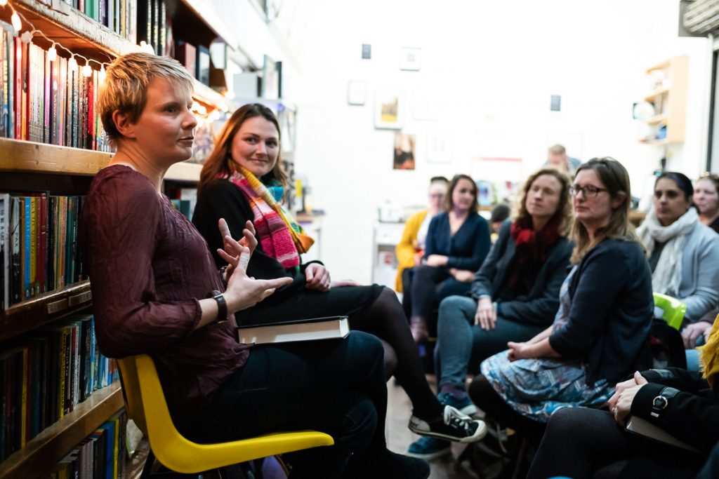 A photograph of Bridget Collins and Rachael Rogan sat in front of bookshelves, and before an audience, engaging in a Q&A