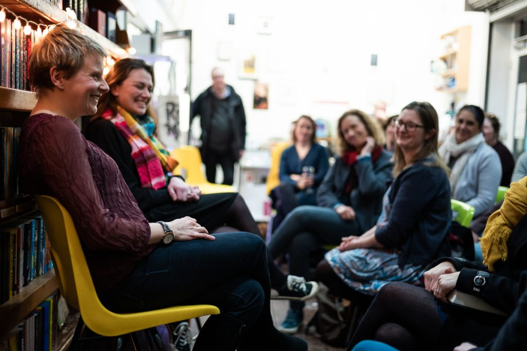 A photograph of Bridget Collins and Rachael Rogan sat in front of bookshelves, and before an audience, engaging in a Q&A - they are both laughing, as are the audience.