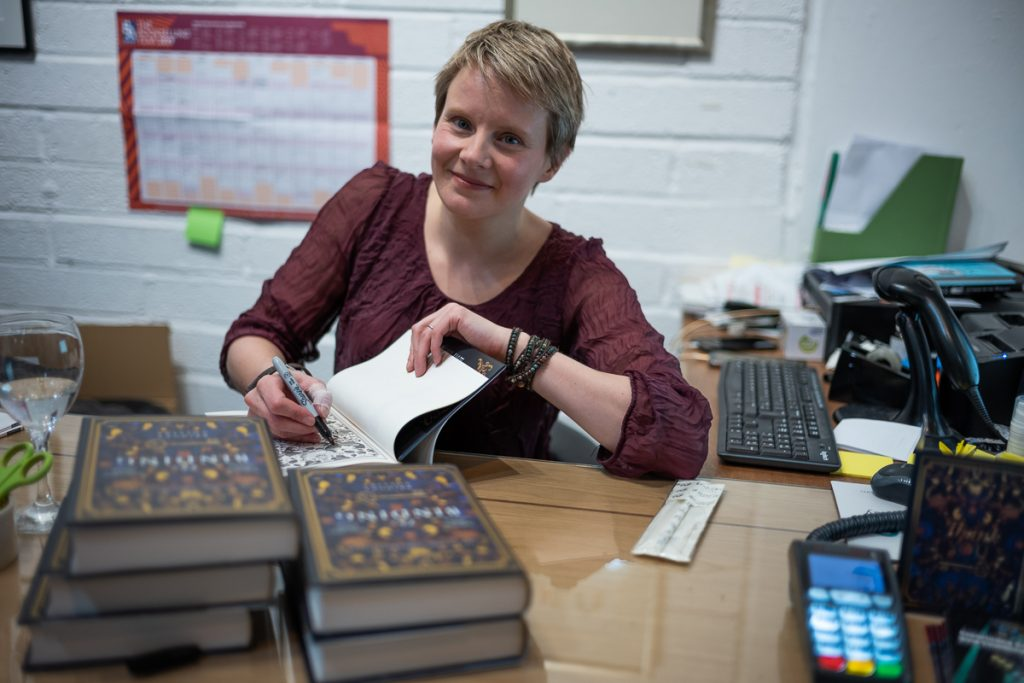 Portrait of a woman signing copies of a book at a bookshop counter.  The woman is best-selling author, Bridget Collins